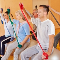 Seniorensport mit Gymnastikband im Fitnesscenter