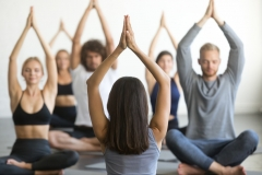 Group of young sporty people sitting in Sukhasana pose